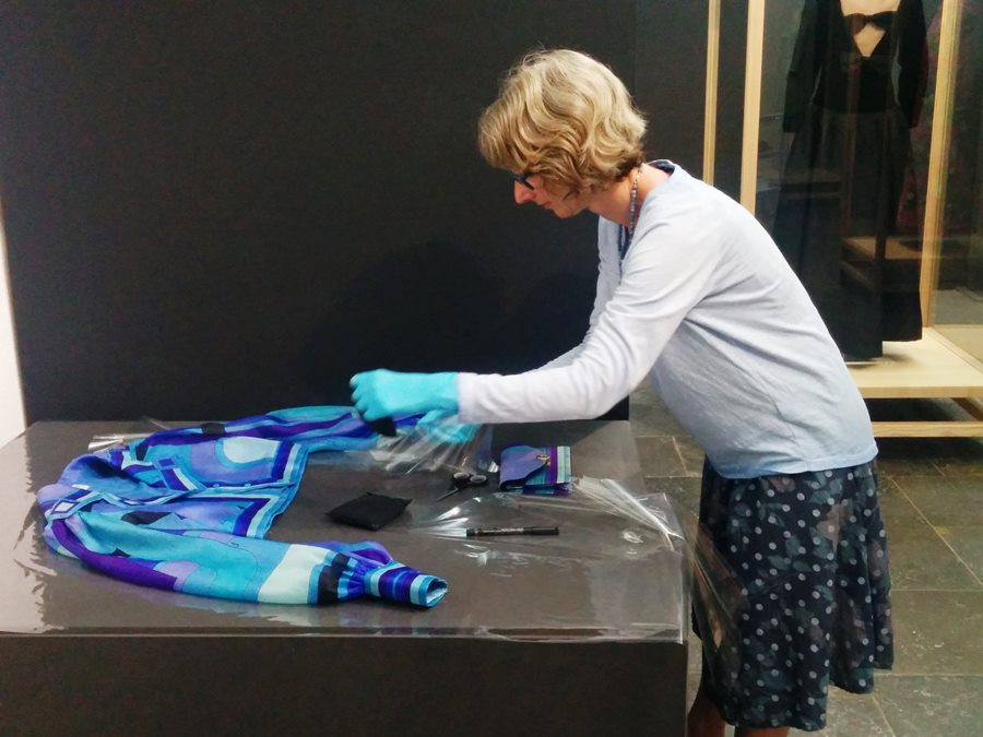 Textilrestauratorin Katharina Sossou bereitet die Präsentation der Mode von Emilio Pucci vor.