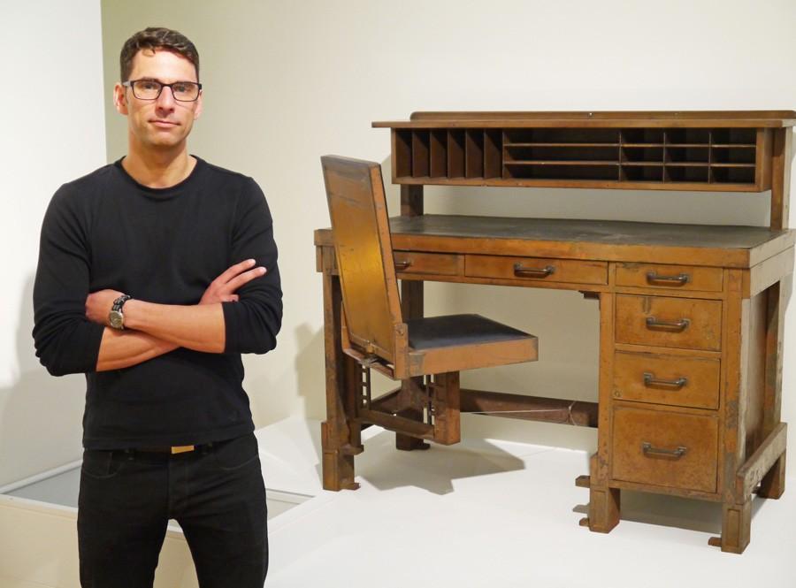 Felix Stark steht vor dem Schreibtisch mit integriertem Stuhl aus Metall von Frank Lloyd Wright von 1904.